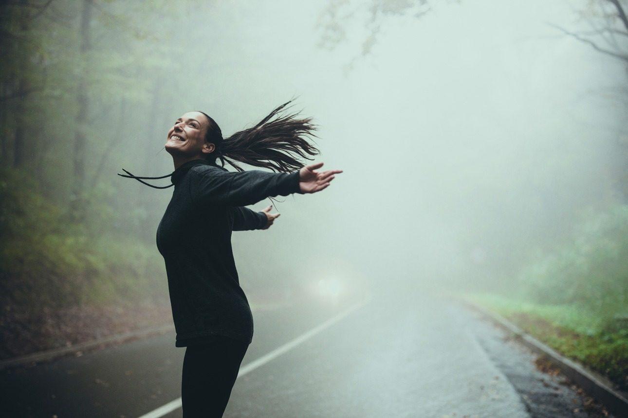 Femme courant dans la brume d'un sous-bois