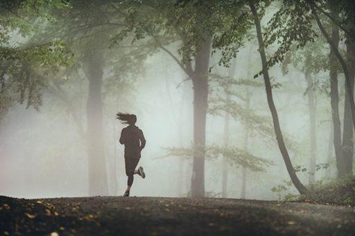 Une jeune femme court dans des sous bois à travers une brume