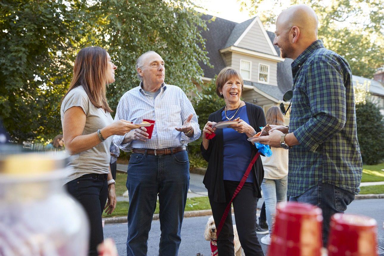 Quatre voisins discutent dans la rue