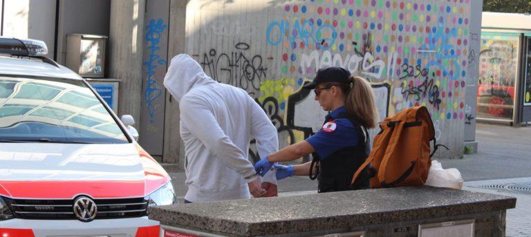 Une policière en train de mennoter un homme vêtu d'un sweet à