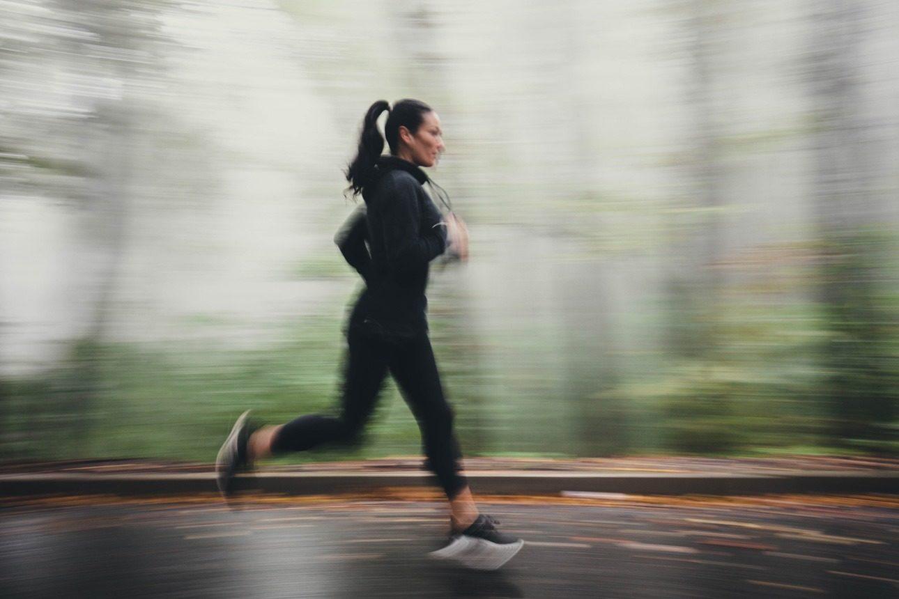 Femme pratiquant la course à pied en forêt par temps de brouillard
